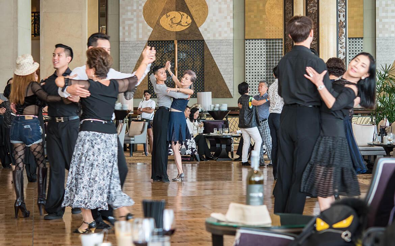 Rige kinesiske kvinder danser tango med unge mænd