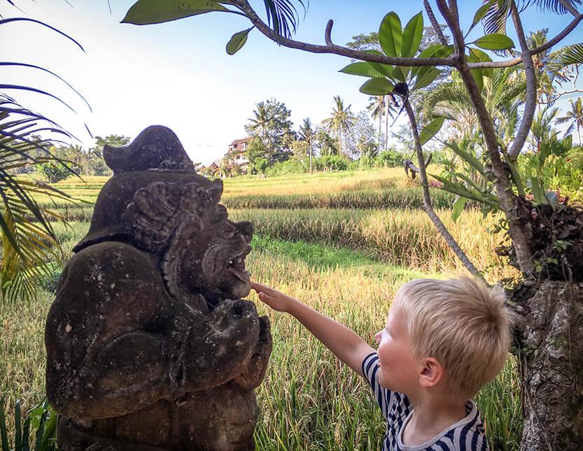 På vores lille tur ud fra Ubud by, ser Sebastian en Balinesisk skulptur, der står midt i det hele. Ubud. Bali.