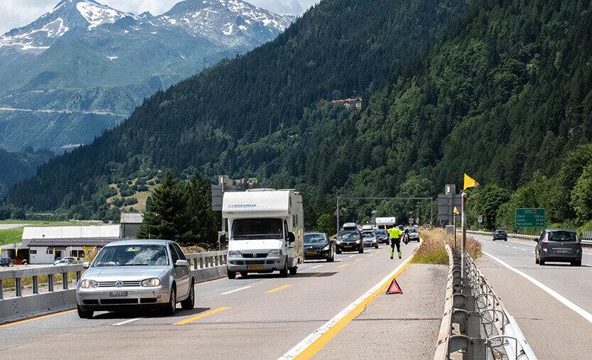 Autohjælperen står midt på motorvejen og vinker bilerne over i den anden side.
