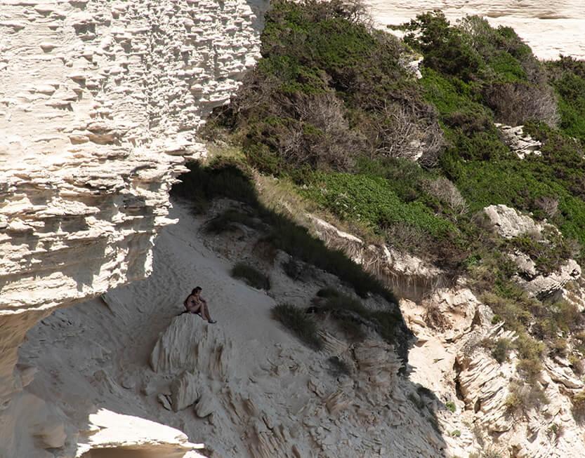 Ungt par der sidder i skyggen af Bonifacios klipper