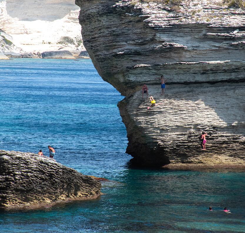 De lokale svømmer ud til klipperne og laver udspring