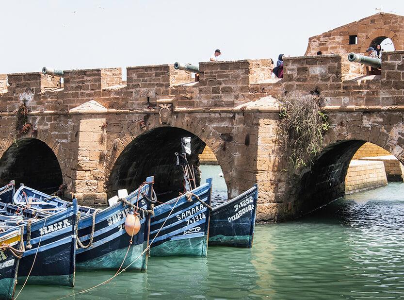 Fisker, der sidder og renser fisk på havnen i Essaouira