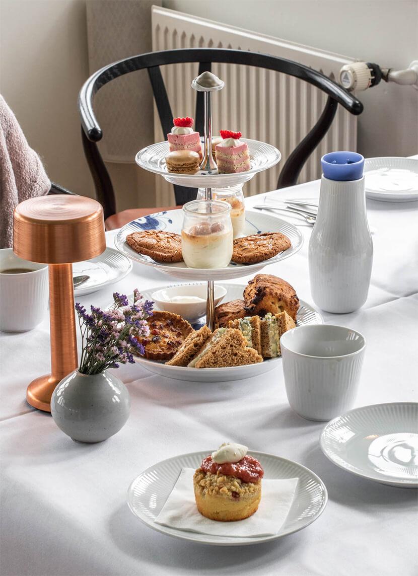 Kagerne og lækkerierne bliver serveret på kagefade med kaffe og te (eller chokolade) til.